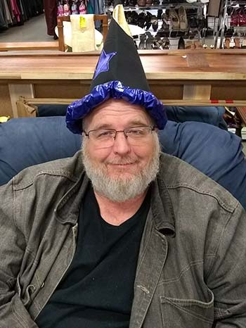 The author wearing a wizard hat and sitting on a couch at a Goodwill store
