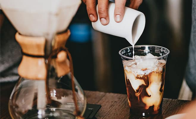 Pouring milk in a plastic cup of cold brew coffee