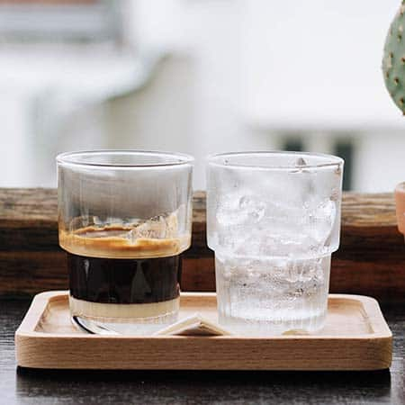 A glass of Vietnamese coffee and a glass of ice