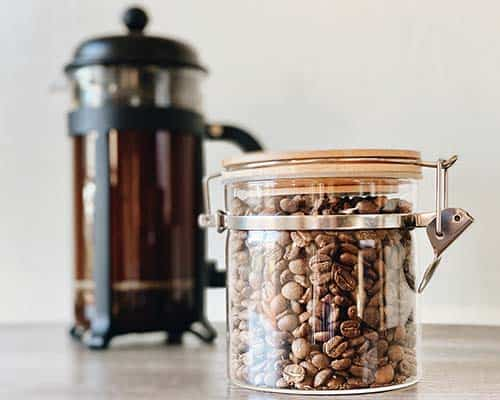 Coffee beans in a glass container and a French press in the background